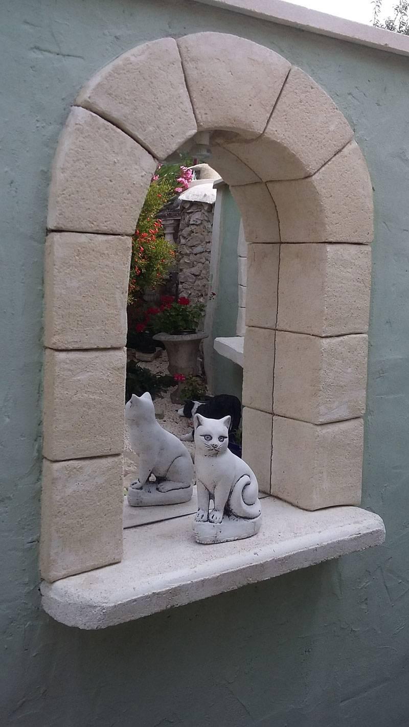 Miroir semi rond en fenêtre trompel'oeil dans un jardin